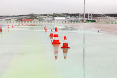 Traffic cones and sprinklers on wet speedway Royalty Free Stock Photos