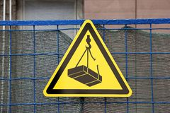 Traffic construction yellow triangular sign warning about falling weigh from height on construction site stock photography