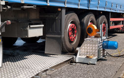 Traffic Control. Police testing brakes on truck, close up on equipment Royalty Free Stock Photo