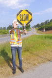 Traffic Controller Slowing Traffic. A traffic Controller holds up a slow sign to slow vehicles during road construction Royalty Free Stock Photography