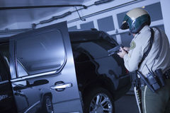 Traffic Cop Aiming Handgun At Car In Garage Royalty Free Stock Images