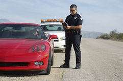 Traffic Cop By Sports Car. Full length of police officer writing a ticket for women driving sports car Stock Image