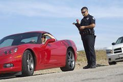Traffic Cop Standing By Sports Car. Low angle view of traffic cop on duty writing ticket for women driving sports car Royalty Free Stock Photography
