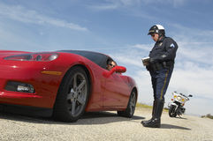 Traffic Cop Talking With Driver Of Sports Car. Low angle view of a traffic cop writing a ticket for driver of sports car Royalty Free Stock Image