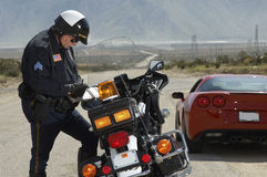 Traffic Cop Writing Against Motorcycle. With sportscar at roadside Stock Images
