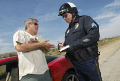 Traffic Cop Writing A Ticket. For driver of sports car Royalty Free Stock Photos