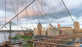 Traffic at dusk on Brooklyn Bridge with Brooklyn buildings Royalty Free Stock Image