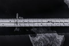 Traffic on elevated road over sea aerial view. Traffic on elevated road over cold sea with ice aerial view. Dark black and white photo stock photo