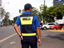 A traffic enforcer stands at a road intersection Stock Photo