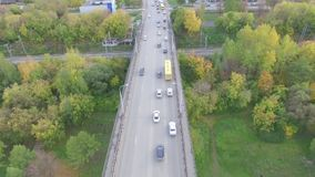 Traffic enters the city from the bridge. Traffic through municipal bridge over the Kama river in the city of Perm, the autumn nature and railroad stock video footage