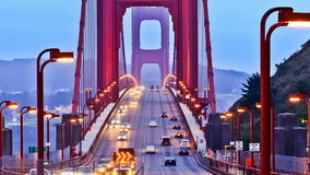Traffic on Golden Gate Bridge. Video clip of traffic traveling north and South across the Golden Gate Bridge in San Francisco USA, at dusk with overhead lights stock footage
