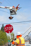 Traffic Guard. A traffic guard holds a stop sign as two power line repairmen hover in the sky, repairling an electric line stock photography