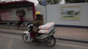 Traffic in Hanoi in Vietnam. Motorbikes traffic in Hanoi, capital of Vietnam, in the winter time. Woman making phone call while driving stock video footage