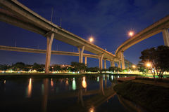 Traffic Highway above a park with reflection on pond Royalty Free Stock Image