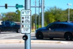Traffic intersection pedestrian crosswalk crossing sign with signal descriptions. Above the request button with cars and lights in the background stock photos