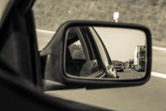 Traffic jam in car mirror in sepia tone Stock Image