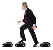 Traffic jam. Funny concept on traffic jam solution - Determined man walking over several cars over a white background royalty free stock images