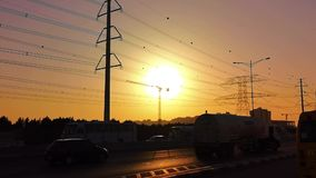 Traffic jam on the highway at an orange sunset - electricity pole transition tower.  stock footage