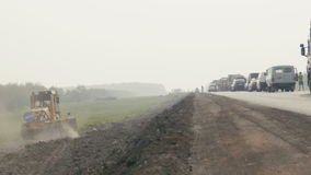 Traffic jam on highway in Russia, construction machinery rides on the side. Wide angle stock footage