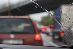Traffic jam in the rain. Traffic jam during heavy rainfall. Shallow depth of field focusing on the rain on the windshield Royalty Free Stock Photos