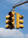 Traffic light. A  yellow traffic light hanging in front of a background of a clear blue sky with some white clouds. the light is red Stock Photo