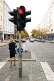 Traffic Light. A woman standing by a red traffic light in Prague, Czech Republic Stock Image