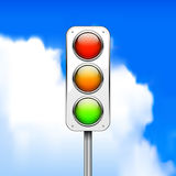Traffic light. Against a blurred background of blue sky with clouds Stock Image