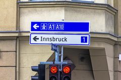 Traffic light with arrows and an exit sign. Salzburg. A traffic light with arrows and an exit sign for 1 and 10 highways in the direction of Innsbruck. Salzburg Stock Image
