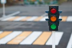 Traffic light on the background of the road and pedestrian crossing in city. Red, yellow and green traffic light. Traffic Laws, stock photography