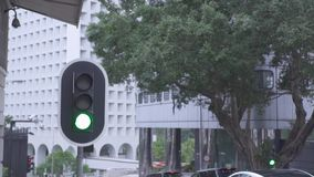 Traffic light on city highway road and cars moving on background urban buildings. Traffic light and car traffic on city. Architecture landscape on urban street stock video footage