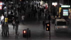 Traffic light is counting down in crowded street at night