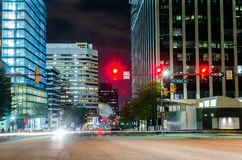 Traffic Light at a Crossroads with Modern Office Buildings in Background. Intersection with Traffic Lights in a Financial District at Night Stock Photo