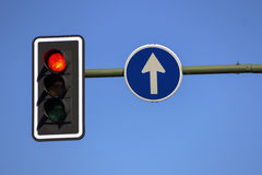 Traffic light and direction sign Stock Images