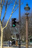 Traffic light, lantern, tree against the blue sky in spring in Paris, where people walk in good weather stock photos