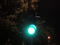 Traffic light at night-time showing green.  Royalty Free Stock Photo