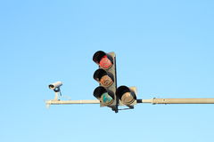 Traffic light. Red traffic light with camera and blue sky behind stock photography