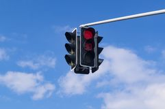 Traffic light with red light signal on sky background. Red traffic signal against a blue sky and clouds. Suspended device with digital display royalty free stock photo