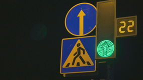 Traffic light regulates cars and pedestrians. Digital traffic light regulates car traffic and pedestrians in night-time stock video footage