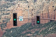A green light on the traffic signal in Sedona. A traffic light and regulatory sign with a mountain in the background in Arizona Stock Image