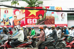 Traffic light stop in Vietnam. A crowd of bikers riding scooters in front of propaganda billboards stock photo