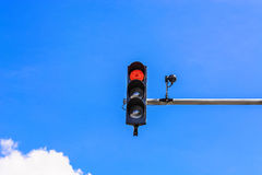 Traffic light and a surveillance camera. A traffic light and a surveillance camera on a pole mounted on the street Stock Images