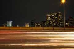 Traffic light trails in modern city at night Stock Images