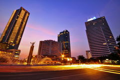 Traffic Light in Twilight time ,Jakarta, Indonesia. Traffic light of speeding cars was shot at a traffic circle with tall buildings around in twilight time Stock Photos