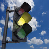 Traffic Light Yellow. Traffic Light in a blue sky with only the yellow light on Stock Image