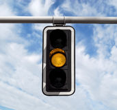 Traffic light - yellow against sky Stock Image