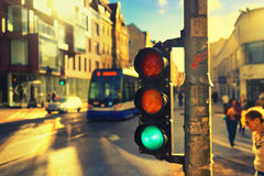 Traffic lights at the crossroads in the sunlight. Pedestrians and tram at the crossroads with traffic lights in the city against the backdrop of facades of Royalty Free Stock Image
