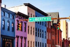 Guide sign at Baltimore street with colored houses. Traffic lights and direction sign at the street of Baltimore downtown with colorful houses royalty free stock photography