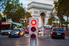 Traffic lights in Paris with Arc de Triomphe in background. Traffic lights in Paris with city traffic and Arc de Triomphe in background Stock Photo