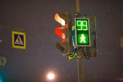 Traffic lights, pedestrian green light and sign at night Stock Photography