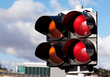 Traffic lights of racing. Double of traffic lights, orange and red, to sports car racing with the cloudy sky as background Royalty Free Stock Photo